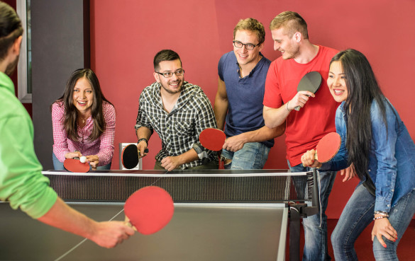 group-of-happy-young-friends-playing-ping-pong-table-tennis-shutterstock_270733406-2-585x369