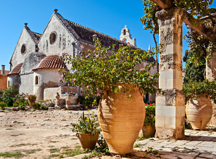 The courtyard of Arkadi Monastery with its ancient covered with twisting grape vine gallery, beautiful bushes in pots and the apse of the church, Crete.