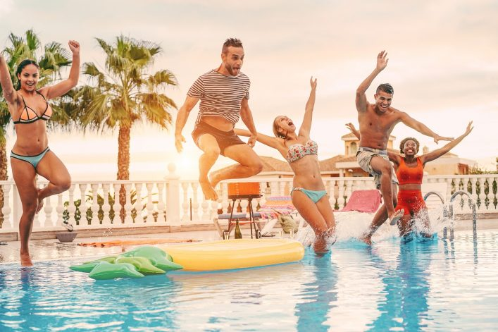 Group of happy friends drinking jumping in pool sunset party outdoor – Young diverse culture people having fun in tropical vacation – Holiday, youth and friendship concept – Main focus on left man