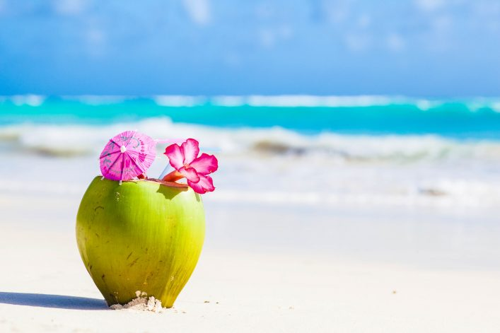 fresh-coconut-cocktail-on-tropical-beach-with-flower-istock_86677841_xlarge-2-1