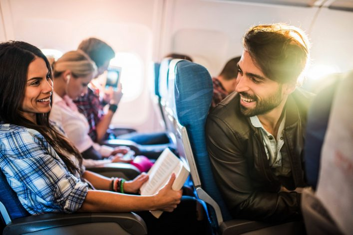 Young smiling man flirting with beautiful woman in airplane.