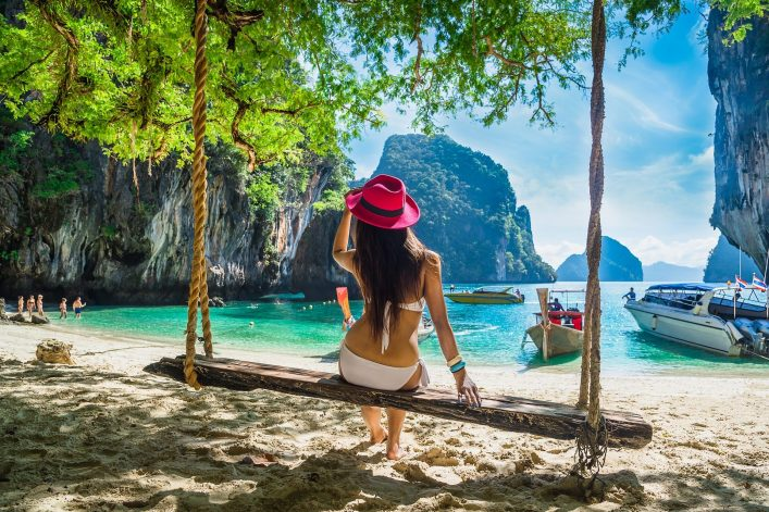 Beautiful-woman-in-bikini-sitting-on-wooden-swing-under-tree-and-looking-destinations-beach-Koh-Lao-Lading-island-An_618044864-e1541594646706