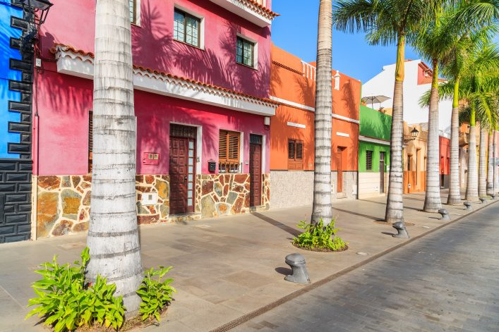 Colourful-houses-and-palm-trees-on-street-in-Puerto-de-la-Cruz-town-Tenerife-Canary-Islands-Spain-shutterstock_341462501