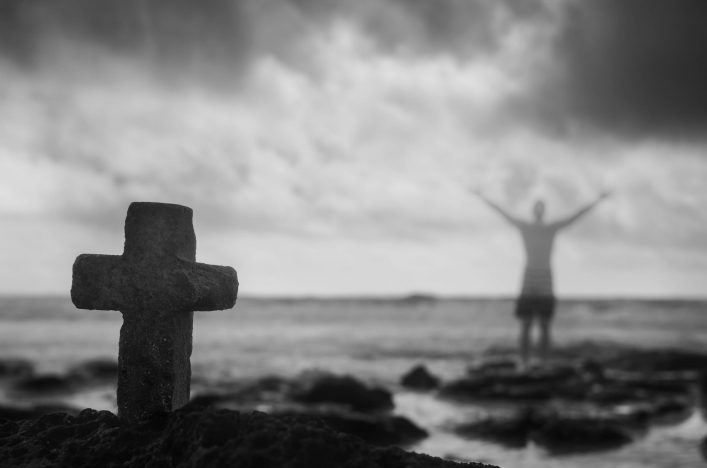 Symbolic crucifix and ghosted man with arms raised.