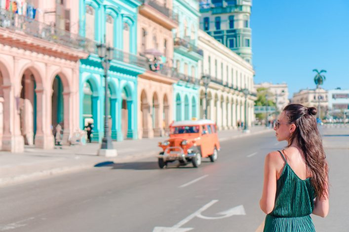 Happy woman in popular area in old Havana, Cuba. Young girl traveler background colorful houses