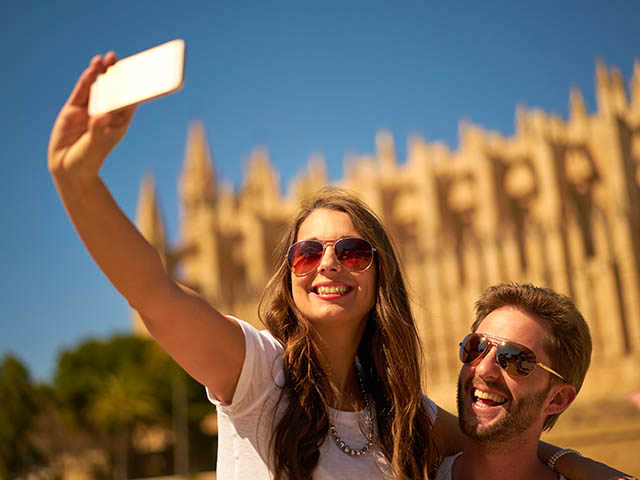 couple-taking-selfie-in-front-of-cathedral-istock-612635642-1