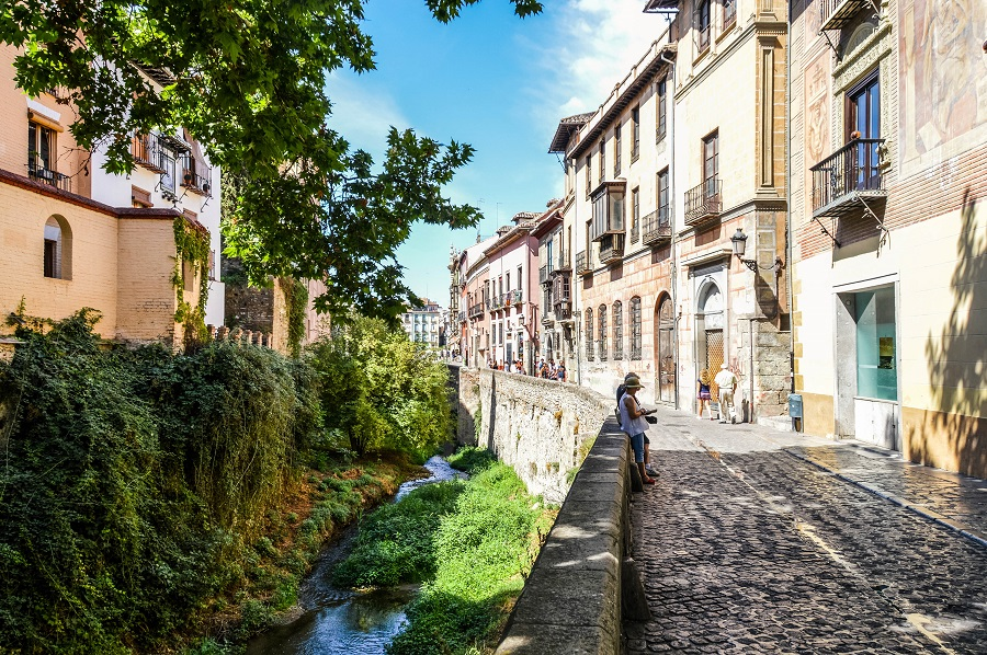 Granada, Spain - August 13, 2015: Walkway along the river in Granada, Spain. Picture taken during the day, and features tourists walking down the street and checking out the shops.