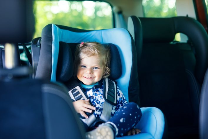 Adorable baby girl with blue eyes sitting in car safety seat. Toddler child going on family vacations and journey.