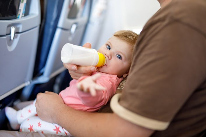 Dad holding his baby daughter during flight on airplane going on vacations