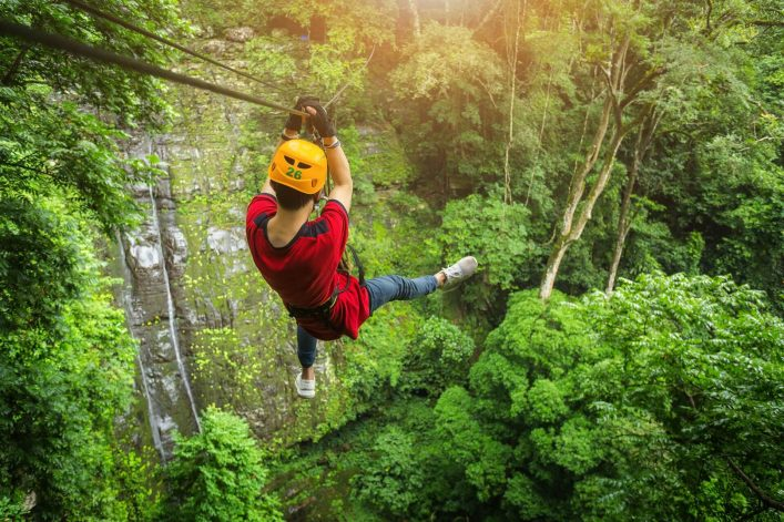 Freedom-adult-Man-Tourist-Wearing-Casual-Clothing-On-Zip-Line-Or-Canopy-Experience-In-Laos-Rain-Forest-shutterstock_690320167