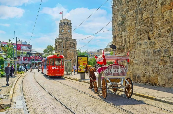 EDITORIAL-ONLY-eFesenko-The-trams-and-horse-carriages-in-Cumhuriyet-avenue-next-to-the-Clock-Tower-Saat-Kulesi-and-preserved-ramparts-on-May-6-in-Antalya.-shutterstock_653551537