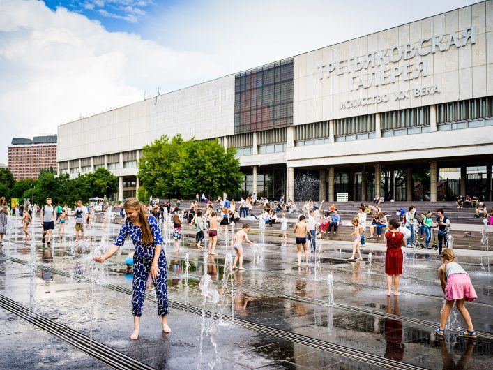 Moscow, Russia –  July 15, 2017: People enjoy summer hot day and playing with fountain's water in front of Tretyakov art gallery