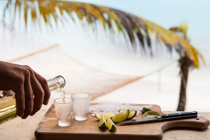 bartender's hand pouring tequila at a tropical Caribbean beach
