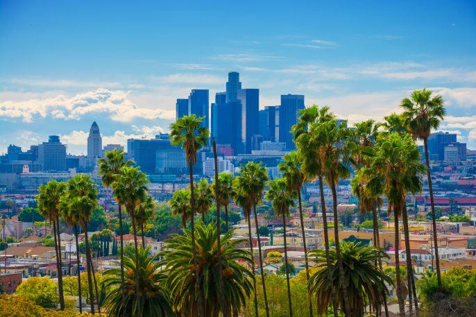 Los Angeles Skyline Backlit Aerial with Vivid Green Palm Trees