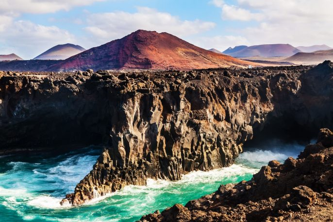 Los-Hervideros-coastline-in-Lanzarote-with-waves-and-volcano-shutterstock_167743202