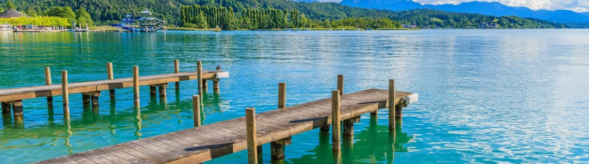Wooden-pier-for-mooring-boats-on-Worthersee-lake-on-beautiful-summer-day-Austria-shutterstock_294768299